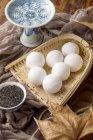 Klebrige Reisbällchen in Weidenbehälter, Trockeneblätl und Sesamsamen auf dem Tisch — Stockfoto