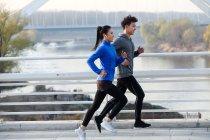 Вид сбоку на молодую пару спортсменов, бегущих вместе у реки — стоковое фото