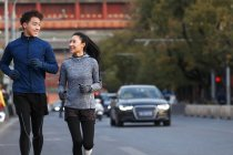 Happy sporty young asian couple smiling each other and running together on street — Stock Photo