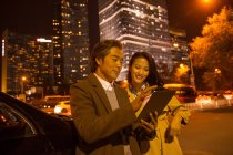 Happy asian couple looking at tablet near car at evening — Stock Photo