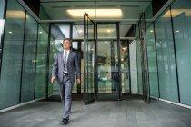 Opinião cheia do comprimento do homem de negócios asiático maduro no desgaste formal perto do prédio de escritórios — Fotografia de Stock