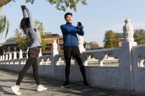 Young asian couple stretching on street before workout — Stockfoto
