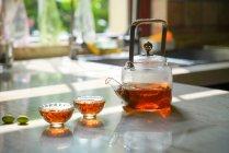 Vista de primer plano del juego de té de vidrio con hervidor de agua y vasos de vidrio en la mesa - foto de stock
