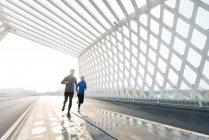 Полный обзор молодых азиатских мужчин и женщин в спортивной одежде, бегающих вместе по мосту — стоковое фото