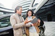 Gli uomini d'affari sorridenti che usano targa vicino ad auto a parcheggio di centro commerciale moderno — Foto stock