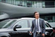 Sonriente maduro asiático hombre de negocios en formal desgaste celebración smartphone al lado de coche - foto de stock