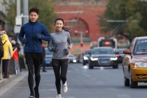 Jovem asiático casal de joggers sorrindo para câmera enquanto correr juntos na rua — Fotografia de Stock