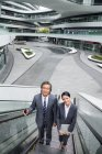 Asian business people on escalator in modern business center — Stock Photo