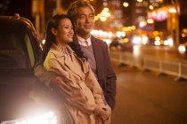 Felice coppia asiatica in piedi vicino auto alla sera — Foto stock