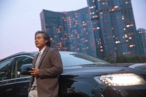 Nachdenklicher Asiate lehnt an Auto und hält Smartphone in der Hand — Stockfoto