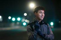 Улыбающийся молодой азиатский бегун в наушниках, стоящих на улице и глядя в сторону в ночном городе — стоковое фото