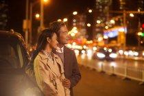 Feliz pareja asiática de pie cerca del coche por la noche - foto de stock
