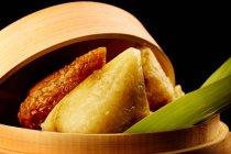 Vue rapprochée de délicieux riz gluant enveloppé dans des feuilles de bambou — Photo de stock