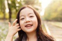 Портрет очаровательного азиатского ребенка, смотрящего в камеру на улице — стоковое фото