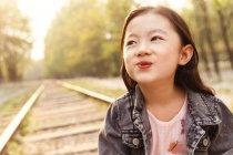 Ritratto adorabile asiatico bambino smorfia vicino ferrovia — Foto stock