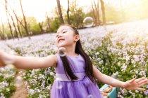 Adorable asiático niño en vestido captura jabón burbujas en flor campo - foto de stock
