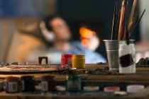 Close-up view of art tools and man in headphones resting behind, selective focus — Stock Photo