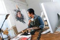Задумчивый азиатский художник держит палитру и пьет кофе в студии — стоковое фото