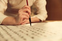 Nahaufnahme einer Frau mit Kalligrafie-Pinsel und chinesischen Schriftzeichen — Stockfoto