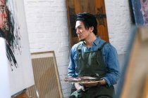 Focused young male artist in apron holding palette and looking at picture in studio — Stock Photo