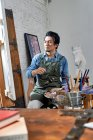 Серьезный мужчина в фартуке держит палитру и живопись картины в студии — стоковое фото