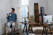 Pensoso asiatico uomo holding tazza di caffè e guardando lontano in arte studio — Foto stock