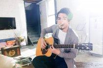 Красивий Азіатський людина грає акустична гітара і дивлячись на камеру в домашніх умовах — стокове фото