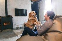 Opinião lateral o homem asiático feliz que senta-se na cadeira do saco de feijão e que joga com o cão em casa — Fotografia de Stock