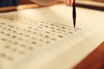 Abgeschnittene Aufnahme einer Frau, die chinesische Schriftzeichen mit Kalligrafie-Pinsel schreibt — Stockfoto