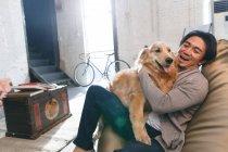 Счастливый мужчина сидит на стуле из фасоли и играет с собакой дома — стоковое фото