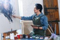 Konzentrierter asiatischer Künstler in Schürzenmalerei Porträt im Atelier — Stockfoto