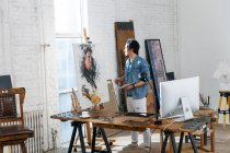 Focused male artist in apron holding palette and painting portrait in studio — Stock Photo
