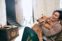 Красивый азиатский мужчина, сидящий в кресле из бобов и обнимающий собаку дома — стоковое фото