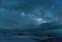 Изумительные заснеженные горы и величественное звездное небо в ночное время — стоковое фото
