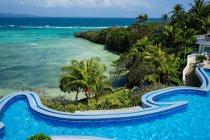 Vista de ángulo alto de la piscina y palmeras verdes en la costa del mar en Koh Samui, Tailandia - foto de stock