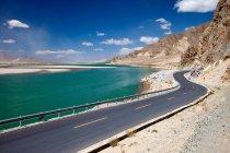 Route asphaltée vide, lac et montagnes au soleil, Tibet — Photo de stock