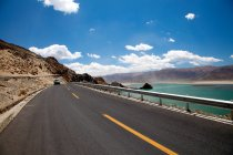 Car driving on asphalt road near body of water and scenic hills at Tibet — Stock Photo