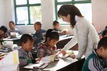 Insegnante femminile rurale cinese e alunni in classe — Foto stock