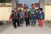 Feliz chino rural pupilos llegar a casa de la escuela - foto de stock