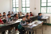 Focused Chinese school students sitting at desks and studying in rural primary school — Stock Photo