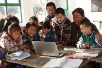 Сельская учительница и ученики вместе используют ноутбук в школе — стоковое фото