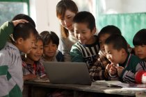 Profesora rural y alumnas chinas utilizando ordenadores portátiles juntas en la escuela - foto de stock