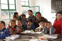 Insegnante donna rurale e allievi cinesi felici sorridenti alla macchina fotografica in classe — Foto stock