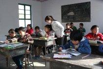 Insegnante donna rurale che guarda gli alunni che studiano in classe — Foto stock