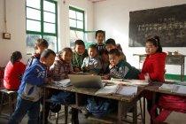 Studenti delle scuole primarie rurali cinesi che usano il computer portatile in classe — Foto stock