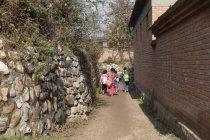 Visão traseira de alunos chineses rurais voltando para casa da escola — Fotografia de Stock