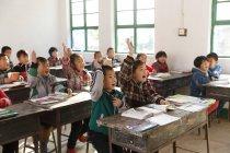 Studenti delle scuole cinesi alzare le mani nella scuola elementare rurale — Foto stock