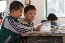 Cadassée d'enseignantes rurales et d'élèves chinois dans la salle de classe — Photo de stock