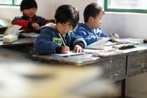 Primary school students sitting at desks in rural primary school, selective focus — Stock Photo