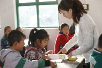 Rural female teacher and chinese pupils in the classroom — Stock Photo